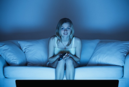 beautiful lonely woman sitting on couch and watching tv photo