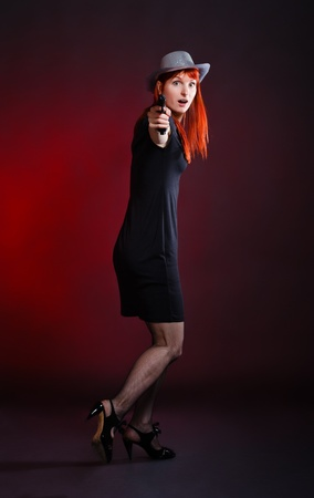 turn away: crazy woman with pistol run away, red background Stock Photo