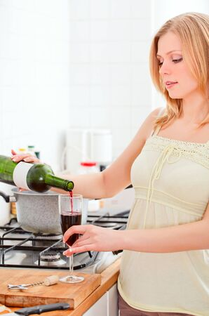 cute young woman pouring wine in kitchen photo