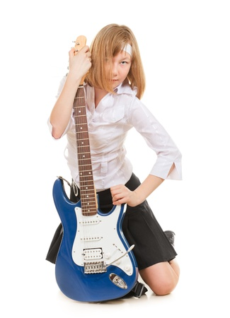 teen girl playing on a guitar, isolated on white photo