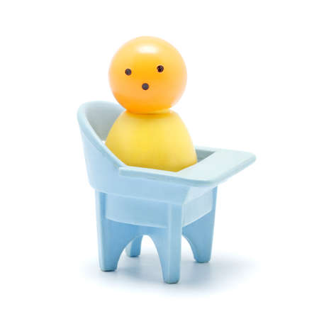suckling: toy baby sitting on chair, isolated on white Stock Photo