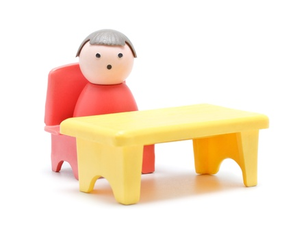 toy man sitting at the table, isolated on white Stock Photo