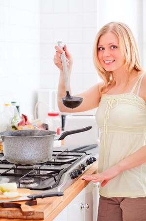 blue white kitchen: cute young woman cooking in bright kitchen