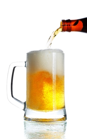 beer pouring from bottle into mug isolated photo