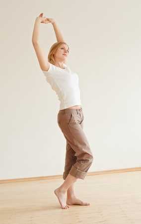 cute young girl walking and stretches at home photo