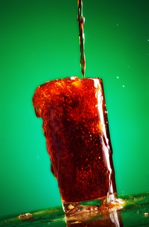 pouring cola in glass over green background photo