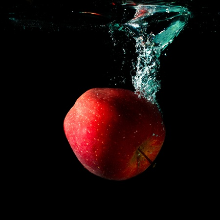 apple falling to water with splash over black background photo