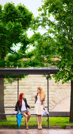 two girls at bus stop, rainy day Stock Photo