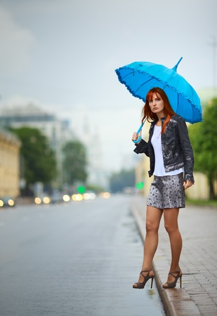legs heels: redhead girls with umbrella waiting a bus