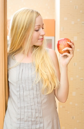 beautiful girl with fresh apple at home photo