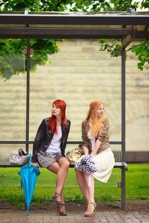 bus stop: two girls at bus stop, rainy day Stock Photo