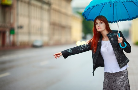 hitchhiking: redhead girls with umbrella hitch-hiking at rainy day Stock Photo