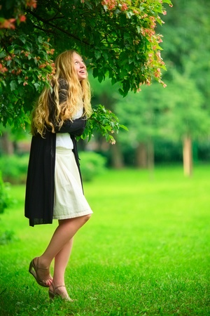 girl hiding from the rain under branch of tree Stock Photo