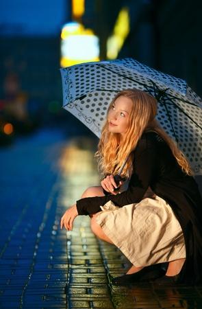 girl with umbrella on street at night photo