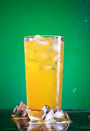glass of orange soda with ice over green background Stock Photo - 10293056