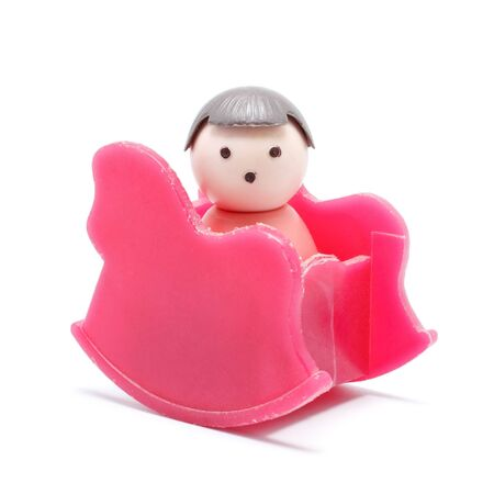 toy baby sitting in rocking chair, isolated on white Stock Photo - 10931346