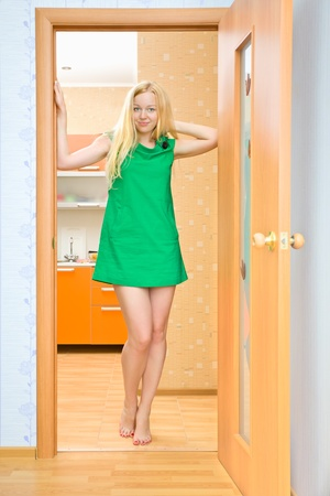 beautiful blond girl in doorway at home Stock Photo