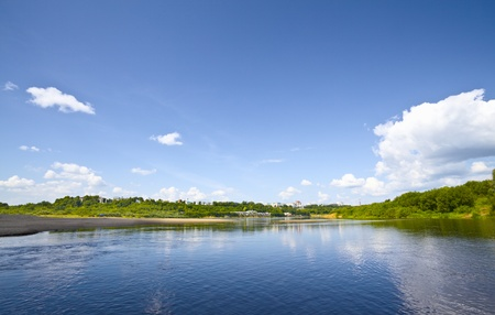 river banks: calm river under blue sky at summer day