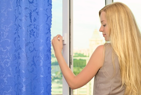 opened: beautiful blond girl standing near opened window Stock Photo