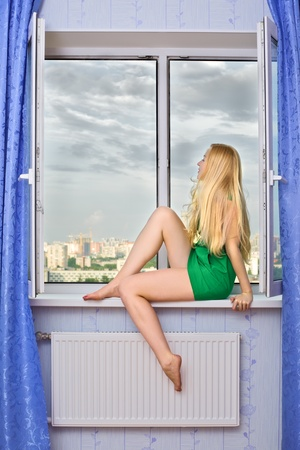 beautiful blond girl sitting on windowsill and looking on city photo