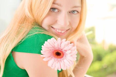 beautiful blond girl with pink gerbera flower, close up photo