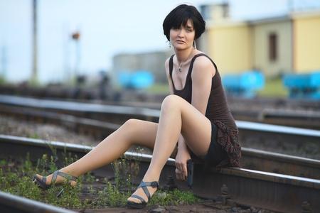 cross leg: hermosa mujer con una pistola sentado sobre ra�les Foto de archivo