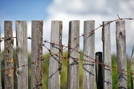 old wooden fence with rusted barbed wire photo