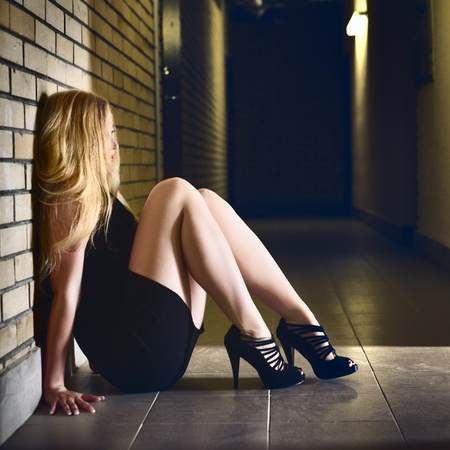 beautiful blond girl sitting on corridor floor