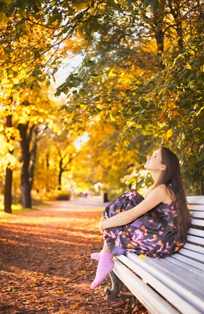 beautiful girl sitting on bench in autumn park photo