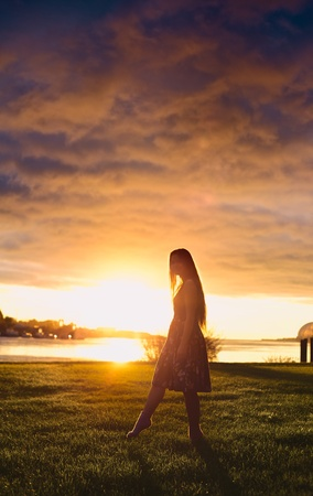 beautiful girl standing on river shore in rays of setting sun photo