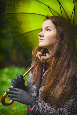 beautiful girl with long hair in autumn rainy forest photo