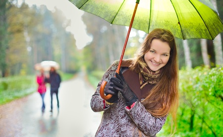 laughing girl and walking couple under rainfall in autumn park photo