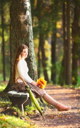 beautiful girl with leaves sitting on bench in autumn park Stock Photo - 11646797