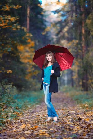 beautiful girl with red umbrella standing in autumn park photo