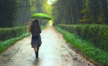 beautiful girl walking under rainfall in autumn park