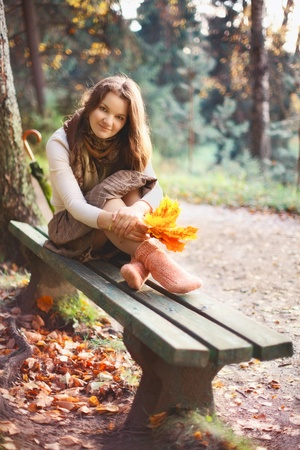 beautiful girl with leaves sitting on bench in autumn park photo