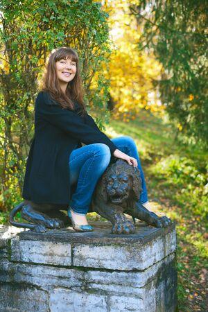 beautiful girl saddle lion sculpture at autumn park photo