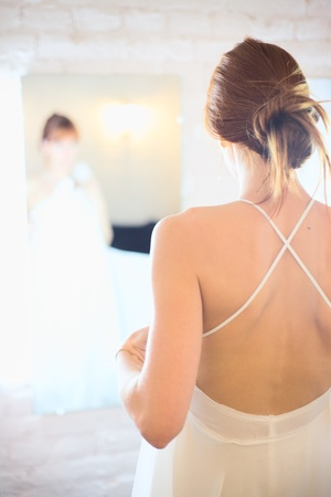 beautiful woman in white wedding dress in front of mirror photo
