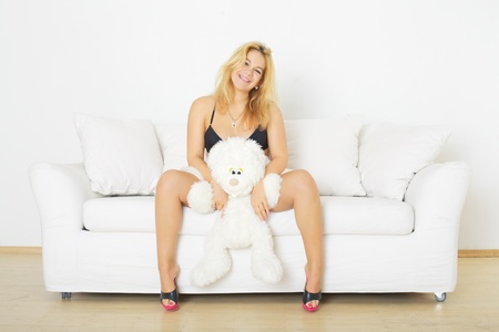 beautiful blond woman sitting on sofa with toy rabbit Stock Photo - 12477190