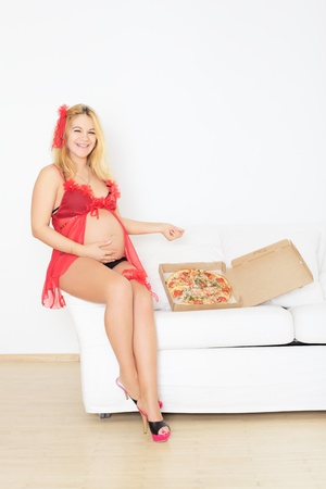 pregnant woman sitting on sofa with pizza photo