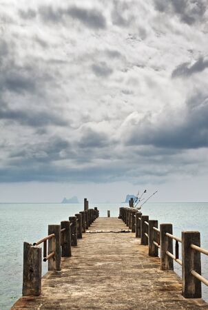 stone pier under dark clouds, Andaman Sea, Thailand photo