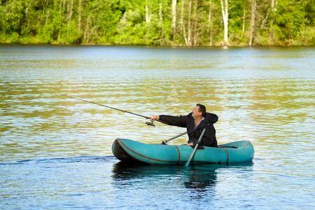 hombre pescando: hombre de la pesca en bote de goma en un lago Foto de archivo