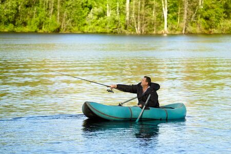 man fishing in rubber boat on a lake Stock Photo