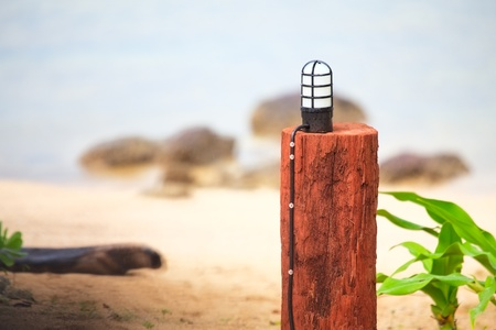 lamp in wooden stand on a beach photo