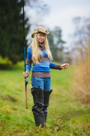 beautiful blond girl fishing in pond at autumn photo