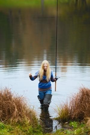fisherwoman: beautiful blond girl fishing in pond at autumn Stock Photo