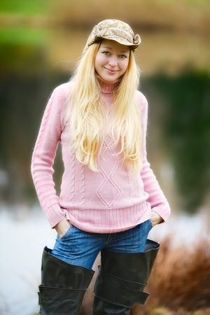 fisherwoman: beautiful girl with long blond hair and pink jersey fishing
