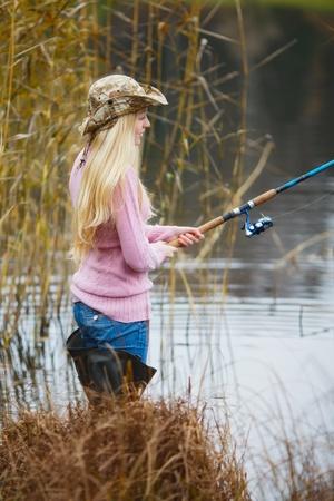 beautiful blond girl in pink sweater fishing photo