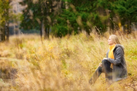 beautiful blond girl sitting on rivershore in autumn forest photo