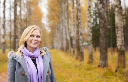 beautiful smiling blond girl in autumn park photo